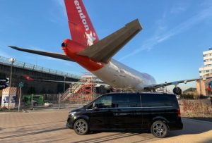 Airport transfer waiting in front of a Corendon plane